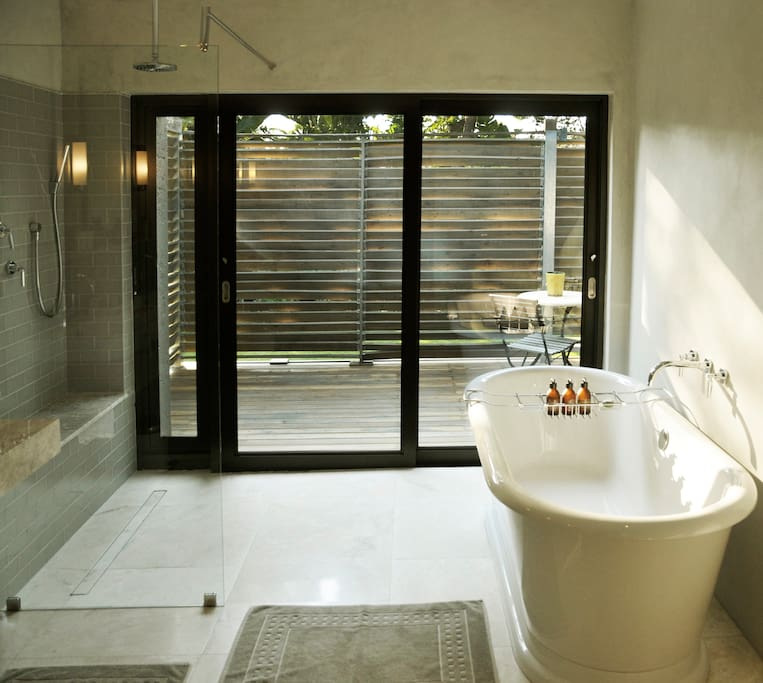 Large marble bathroom with freestanding tub and walk-in shower that open to your private deck.