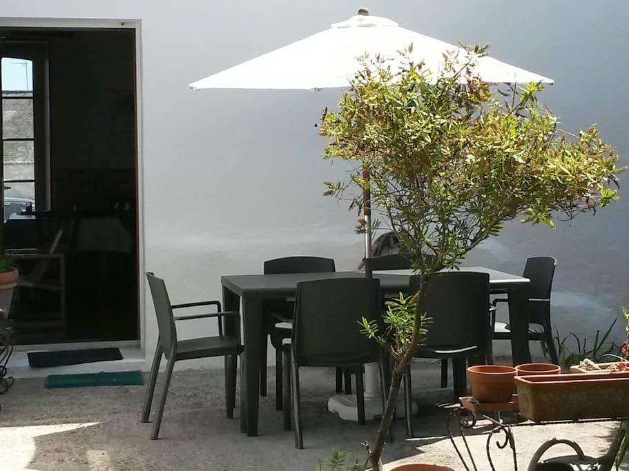 Terrasse côté jardin avec barbecue.