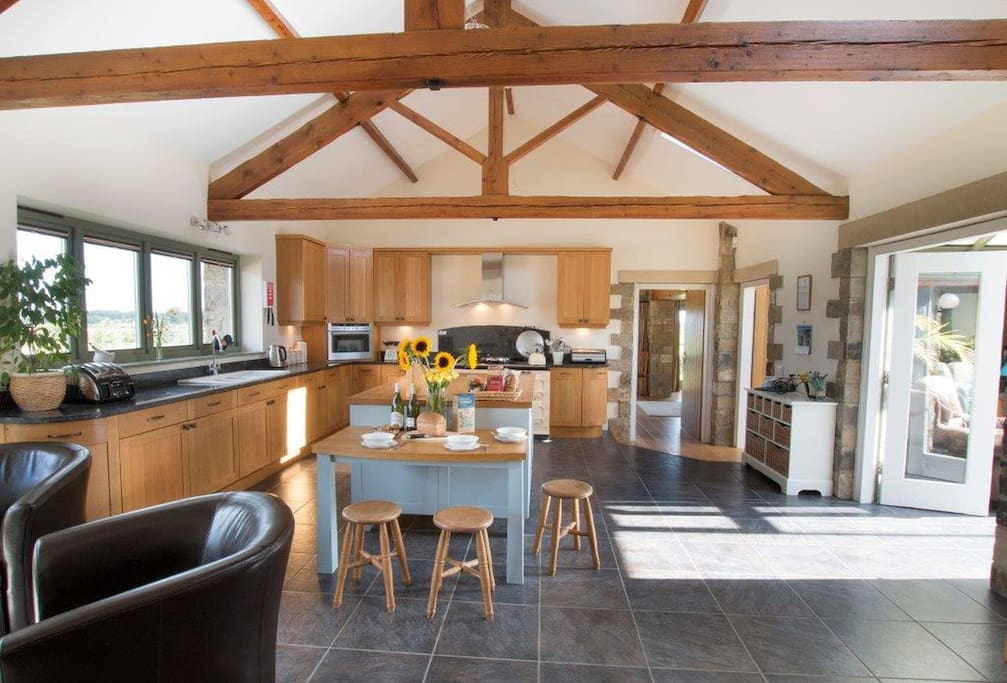 Ground floor: Large kitchen with a four oven cream Aga, electric hob and combination oven, breakfast bar and a family space with a TV