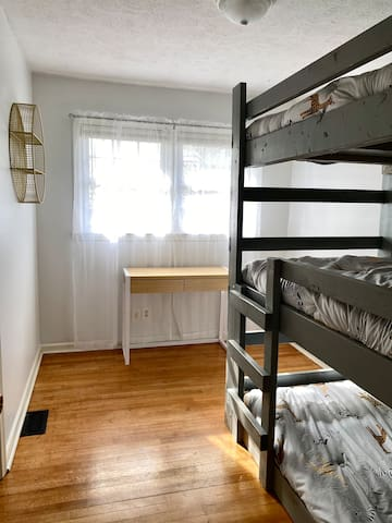 Bedroom 3 has a triple bunk bed, a workspace, and a bookshelf.