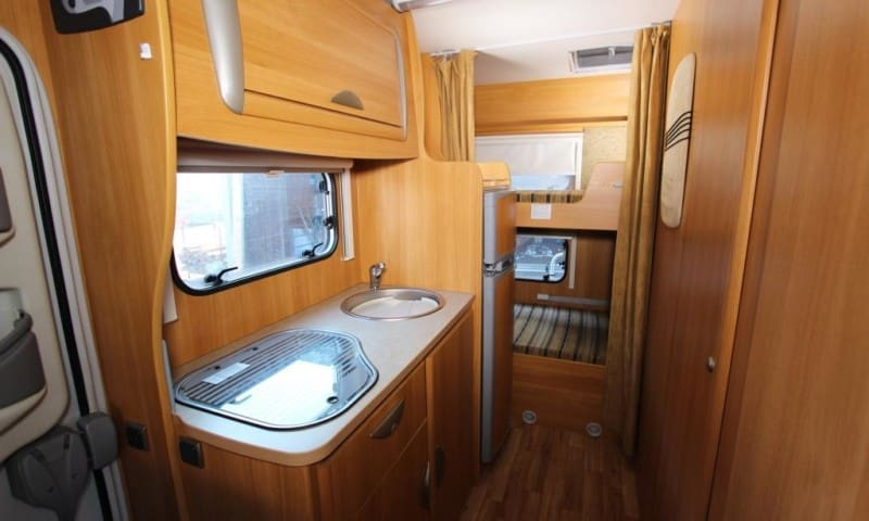 Kitchen area. Two single beds i rear of camper.   A fridge with a small freezer.