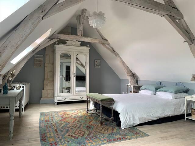 La grande chambre Bleue avec un lit BB, une  commode et une grande armoire bien pratique pour y pendre ses robes et une grande table pour (pourquoi pas) y télétravailler.