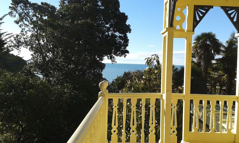 Guests can enjoy a large private balcony which is surrounded by trees and has views out to sea and across the valley.