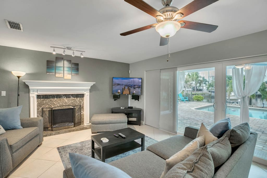 The living room has it all -- comfy seating, flat screen TV, decorative fireplace, and direct access to the gorgeous backyard.
