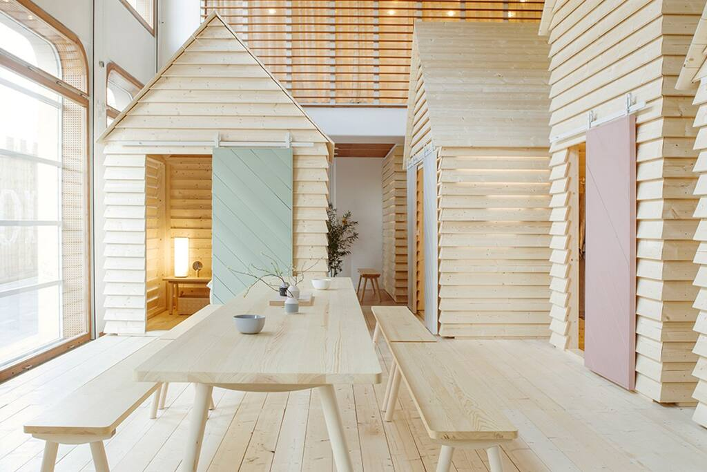 "KOTI (Finnish for ""home"") transforms the Finnish Institute to bring the magic of the communal cottage experience to Paris's Rive Gauche. Each evening, up to 12 guests can book from a selection of six spruce timber aitta. Each day, the installation is open for the public to visit."