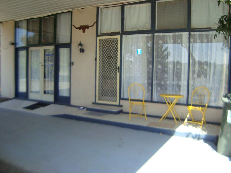Frontage of your apartment under a large carport. Enter thru double glass doors