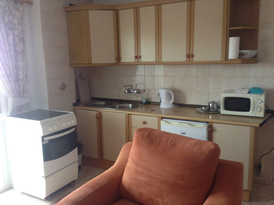 Kitchen area with Full cooker, microwave, electric kettle, fridge and al crockery and cutlery.