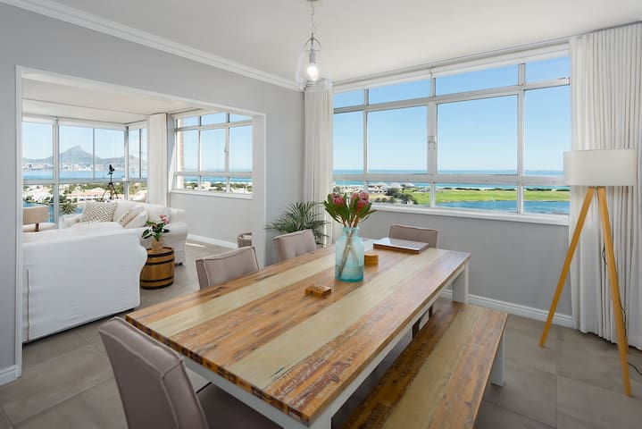 Dining room with expansive views of Table Mountain, Table Bay and Robben Island. Built-in USB wall plug charger in the dining area. (Just bring your cable along.)