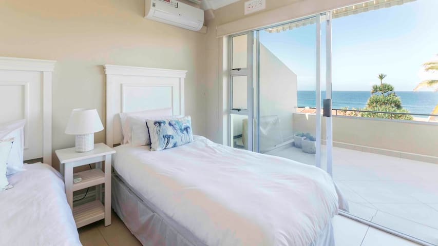 Second bedroom with two single beds, with direct access to the large balcony and views of the ocean
