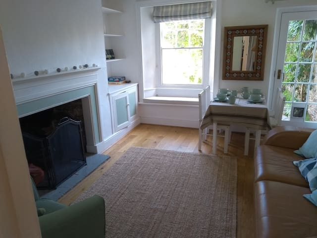 Cosy lounge/dining room with open fireplace, and view to south facing garden.