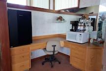 Coffee and tea station with mini fridge and microwave.