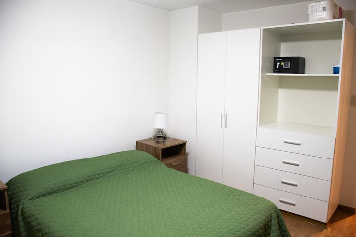 Single bedroom with a full bed, closet, safe box, work desk and chair and a lamp. The bedroom has blackout rollers.
