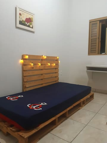 Quarto 2 = uma cama em pallets de solteiro, uma mesinha de estudos com um puf, possui colchão extra, sendo possível dormir mais um hóspede nesse quarto.
