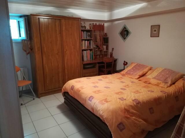 Grande chambre avec bureau, armoire, 2 chevets. Sur le mur face au lit : Près de la porte, 1 meuble avec livres 2 autres armoires (2 penderies et 2 étagères) Près de la fenêtre, 2 petits meubles avec livres.