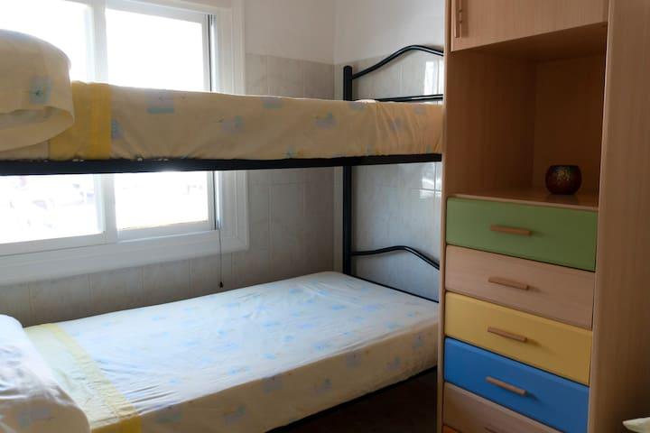 Dormitorio 2.  Una litera y una cama individual.  Con armario y gran cajonera.