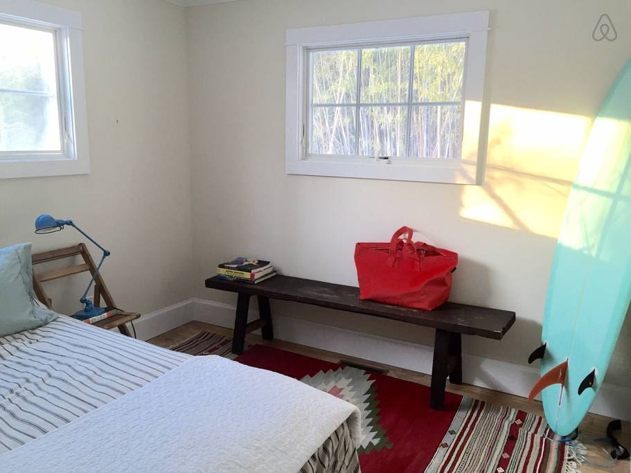 Cozy, light filled main bedroom. Windows look out over the lawn and bamboo trees.