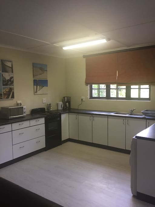 Kitchen fitted with stove, dishwasher and microwave oven.