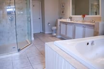 Mather bathroom with separate shower and his and her vanity