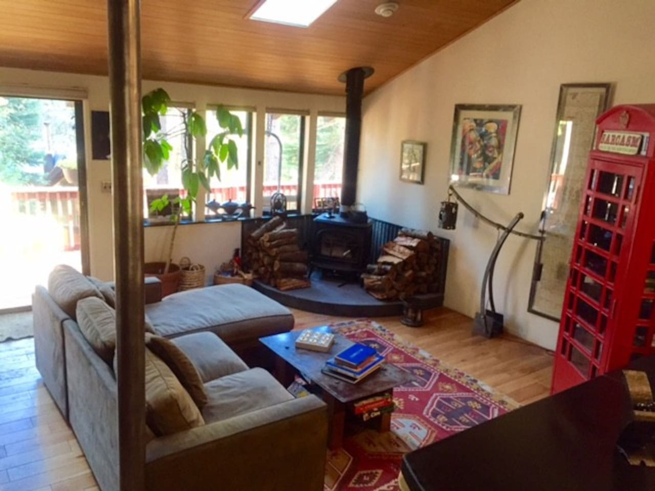 Main lounge area, with a deck that leads to a backyard. Wood stove is a great addition. TV is in telephone booth with books and games for the family.