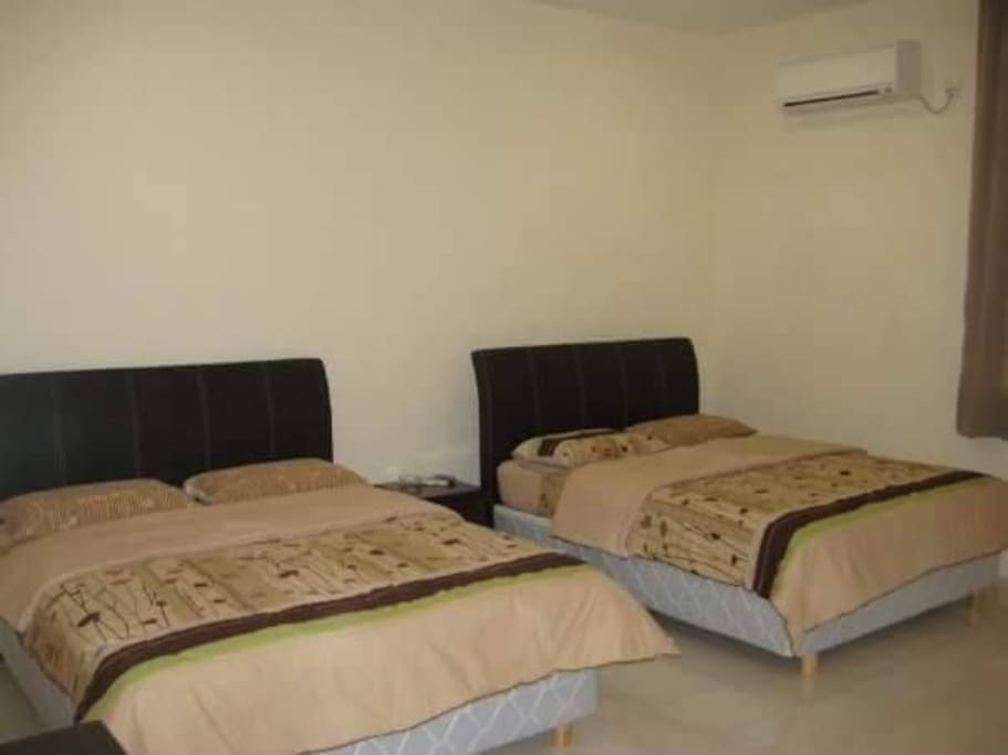 This is the master bedroom with two queen sized bed in it. There is a private bathroom for guests in this room. Air conditioning is available in all rooms.