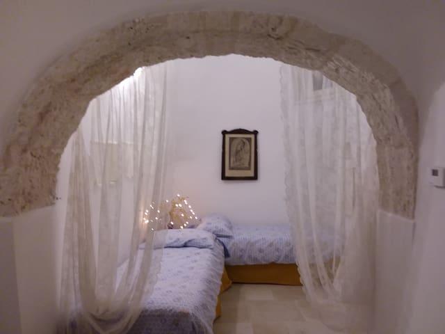 L'alcova con due letti singoli, separata dal resto della casa da un ampio arco in pietra e da tende.