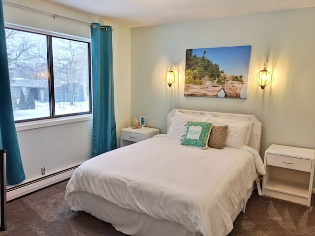 This room with queen bed and closet overlooks the backyard volleyball and playground.