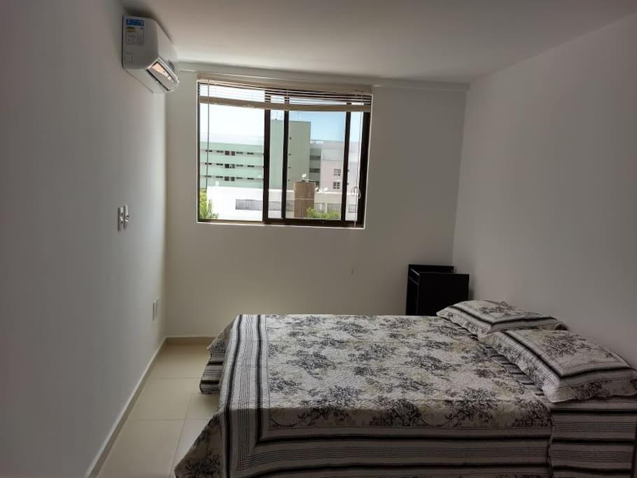 Suíte com cama de casal, ar-condicionado e guarda-roupa de duas portas.