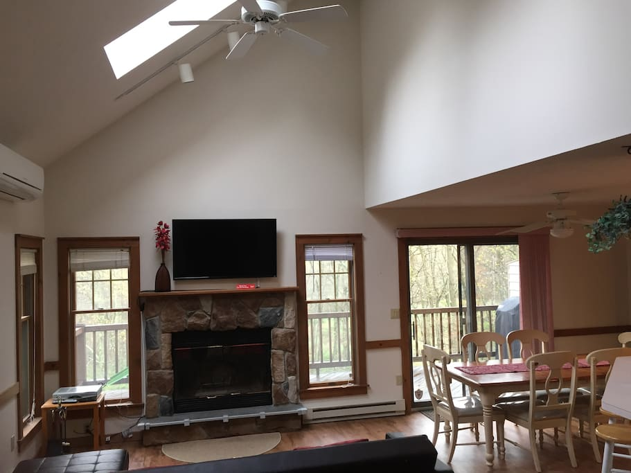 Living room with cathedral ceiling, fireplace, fan and split AC