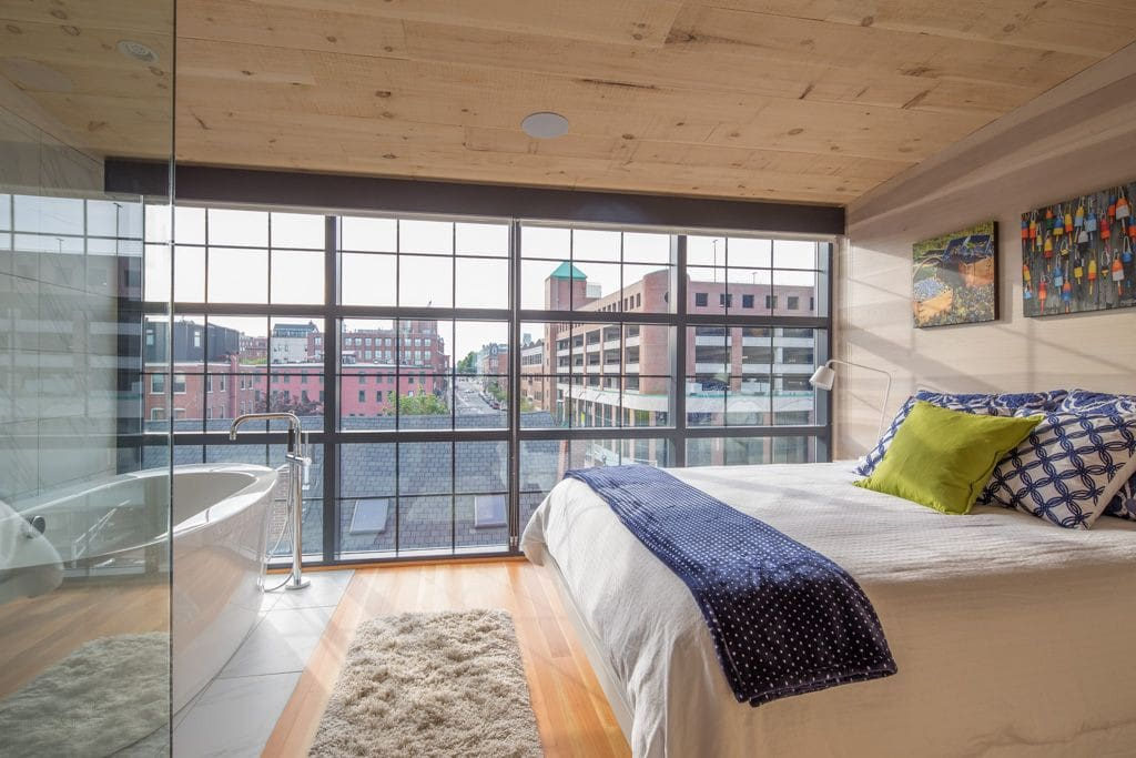 Master bedroom soaking tub and walk-in shower with floor-to-ceiling windows and roller blinds for privacy. Queen bed.