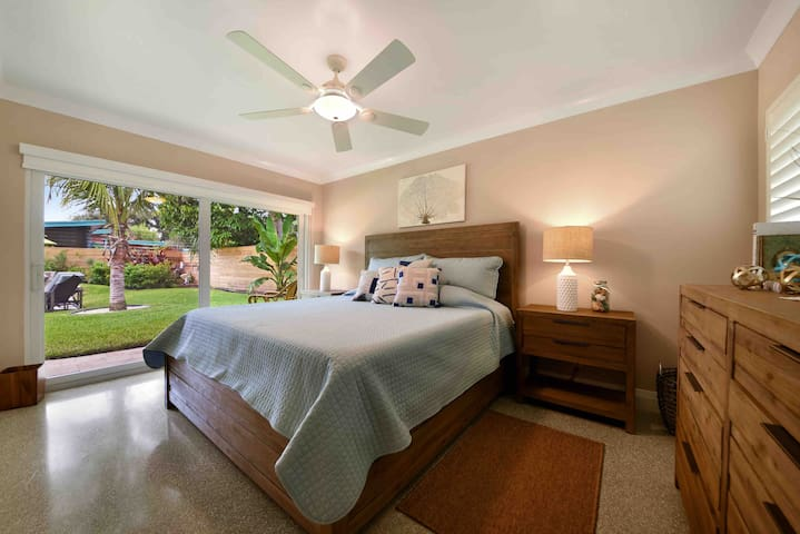 Master bedroom with a flat screen TV on the wall and a comfortable king size bed.