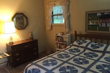 Guest bedroom with a queen bed and handmade quilt.