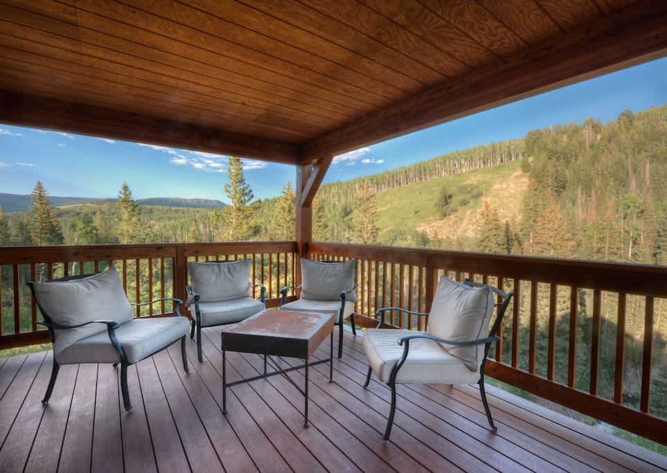 Wild Skies Cabin in NW Colorado Second floor balcony deck overlooking the river and moutnain views during Summer