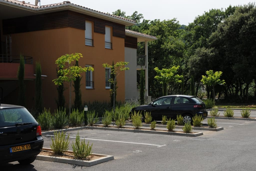 Voorkant appartementencomplex met parkeerplaats binnen omheining