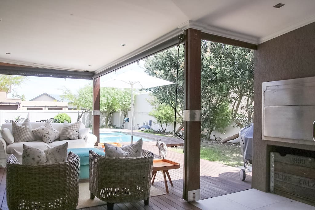 Covered patio with lounge furniture, roller blinds for wind/rain