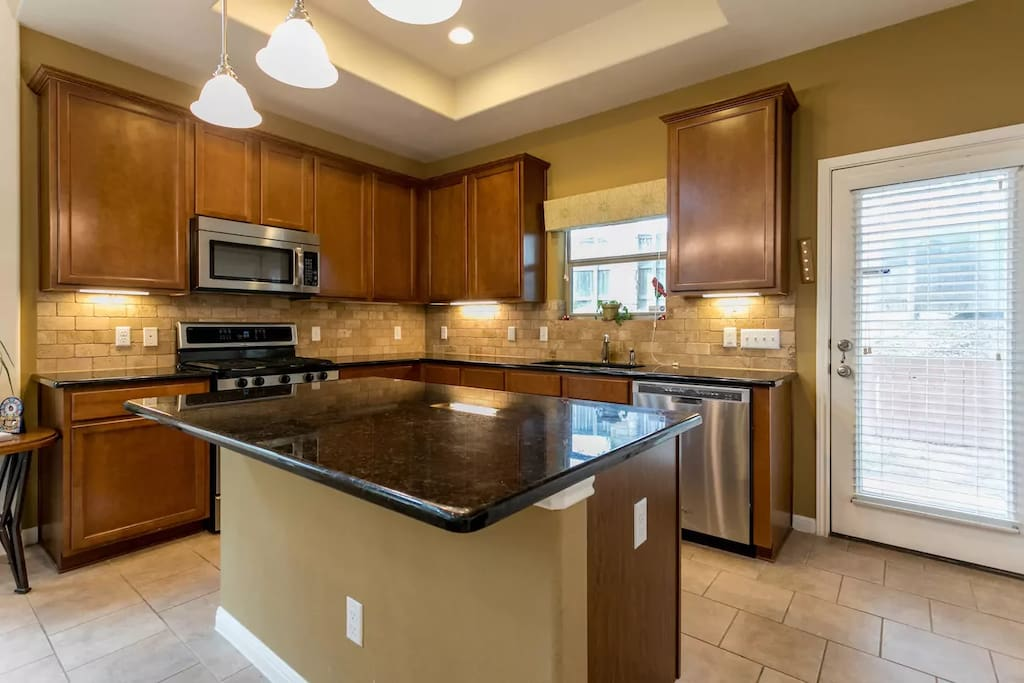 Marble countertops and cabinets full of everything you would need for cooking and baking.