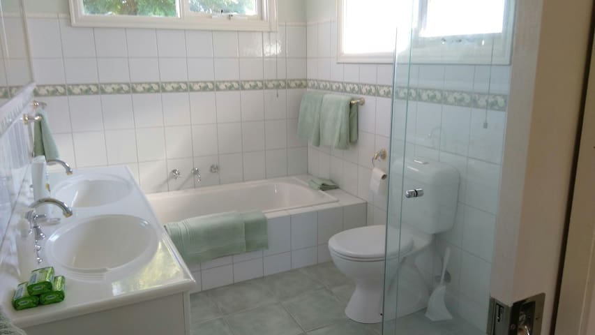 Large modern bathroom with bath, shower  and 2 double basins.