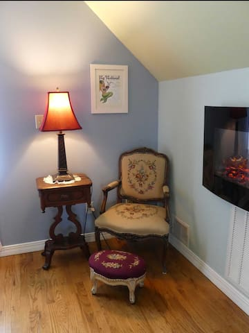 Comfortable reading area next to wall fireplace.