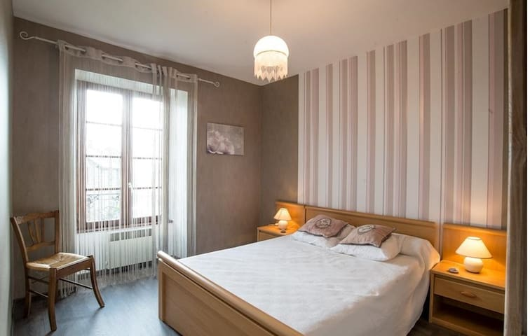 Chambre avec un lit double , deux chevets et une armoire .