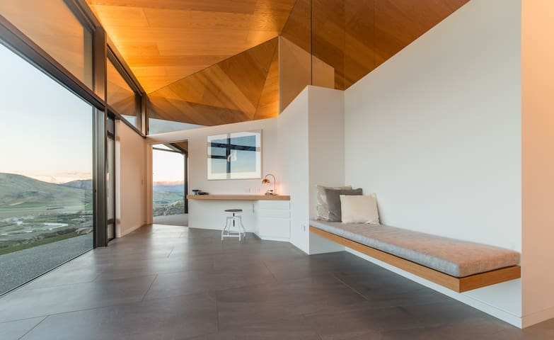 This suspended day seat and unique desk, with angular drawers, lead to the beautiful master bedroom with ensuite. There are extra chairs that can be used here or outside to enjoy the views.