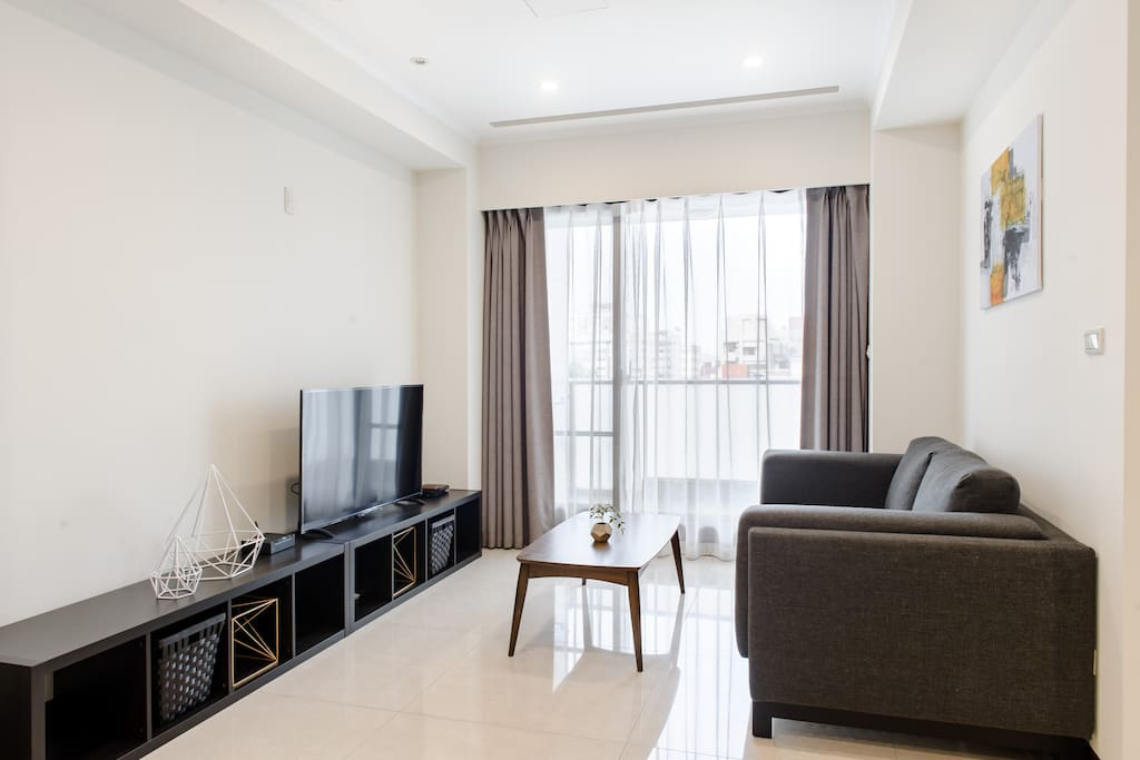 """Living area with 50"""" TV, comfortable sofa and sunlight."""