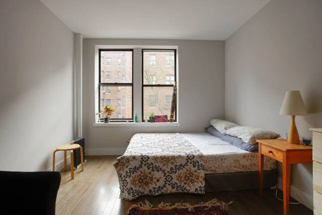 Your room. It's big, warm and cozy and feels like a sanctuary. Candles and natural light. The rugs are from Afghanistan. Wooden decorations from Ethiopia. Futon available for guests. Bedding from Morocco
