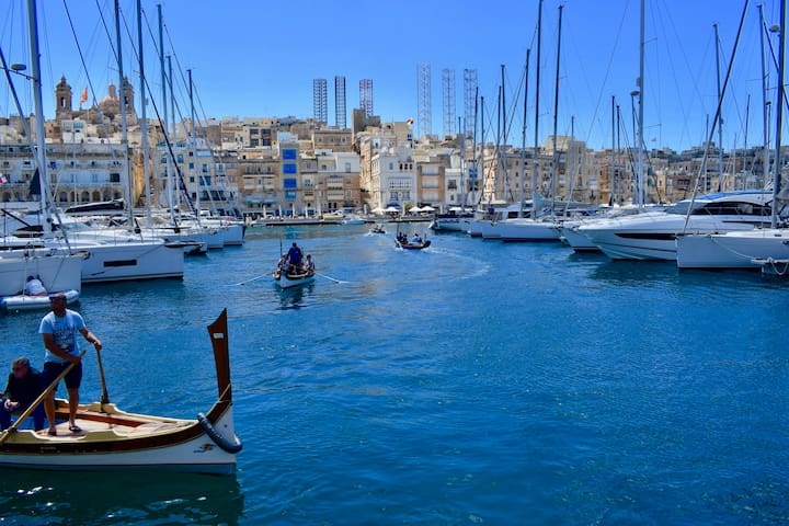 Birgu Waterfront, with traditional Maltese Boats crossing over to Senglea