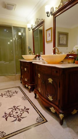 Elegant private washroom loaded with spa bathtub, steam shower, and twin Jade vanities.