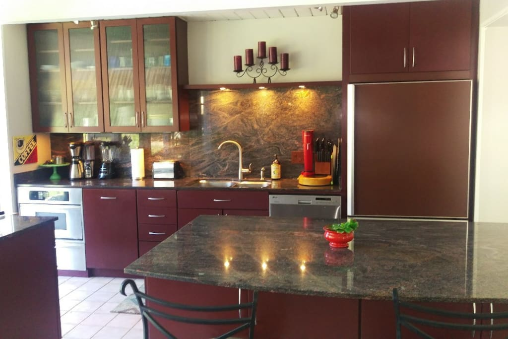 luxury kitchen with granite breakfast bar, stainless appliances, wolf stove with built in grill
