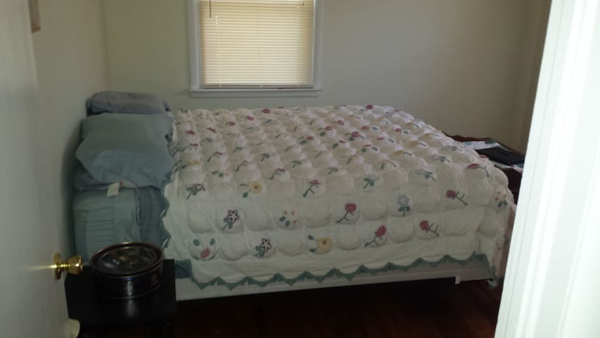 Hardwood floors, comfy queen bed with country quilt.