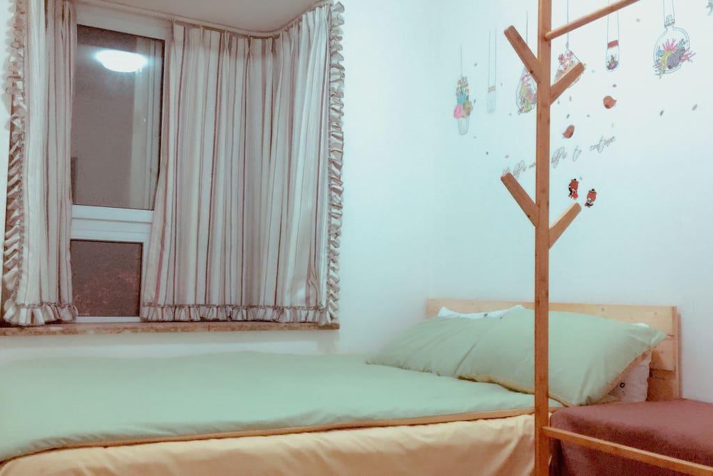 简洁的卧室,有飘窗,外面是临街,但一点不吵