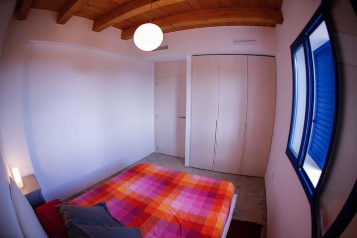 Dormitorio con una cama Queen-Size y armarios empotrados.