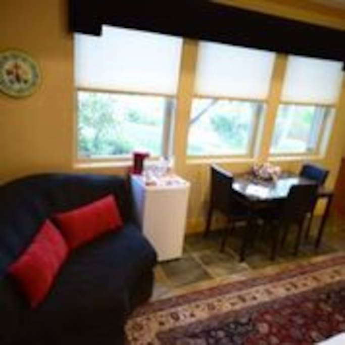 Private sitting area to view TV, stocked refrigerator and table and chairs for eating or work.