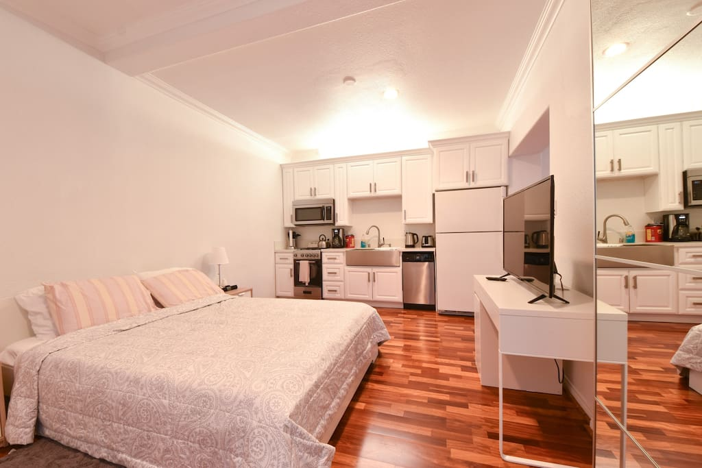 Full view of kitchen, tv, and queen bed