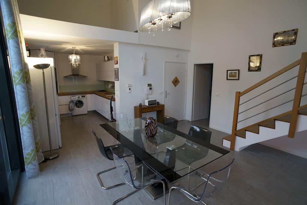 La cuisine s'ouvrant sur la grande table et l'escalier qui conduit à la chambre et salle-de-bain supérieures.